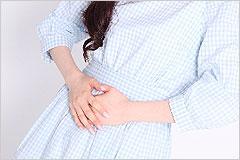 お腹を押さえている水色のワンピースを着た女性の下腹部の写真