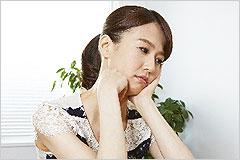 頬杖をついて憂鬱な様子の女性の写真