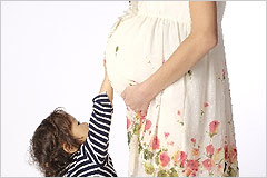 小さな子供が妊婦のお腹にタッチしている写真