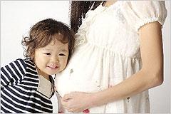 小さな女の子が妊婦のお腹に耳をあてている写真
