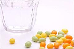 水の入ったコップと色とりどりのサプリメントの写真