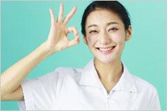 指でOKサインを作っている看護師女性の写真
