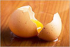 割れた生卵から中身が流れ出ている写真