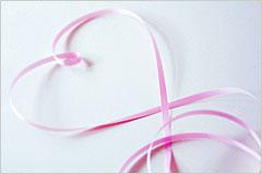 ピンク色のリボンがハートを描くように置かれている写真