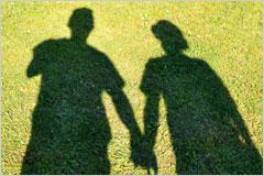 芝生に映る、手を繋いだ男女のシルエット写真