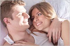 ベッドで方を寄せあって微笑んでいるカップルの写真