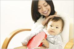 赤ちゃんとハートのオブジェを抱いて微笑んでいる女性の写真