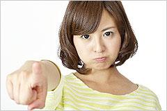 正面を指差して厳しい表情をした女性の写真