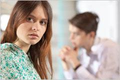 怪訝な表情の女性と奥にいる男性の写真