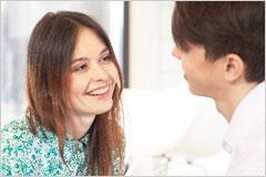 笑顔で男性に話しかけている女性の写真
