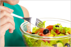 女性の手が、ボウルに入ったサラダを食べようとしている写真