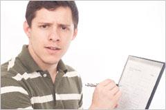 書類を手に驚いた表情の男性の写真