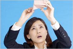 財布をひっくり返して焦っている様子の女性の写真