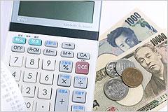 お札と硬貨、電卓が一緒に置かれている写真
