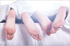 ベッドからのぞいた男女の足裏の写真