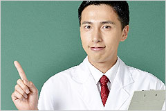 黒板を前に指差ししている白衣の男性の写真