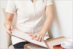書類を手に何かを説明している白衣の女性の写真