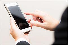 スマートフォンを操作している手の写真