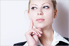片手を頬にあてて考え事をしている女性の写真