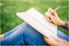 膝の上にノートを乗せて何科書いている女性の写真