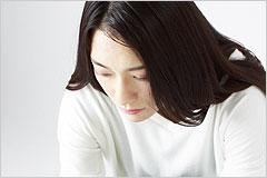 うつむいて暗い表情の女性の写真